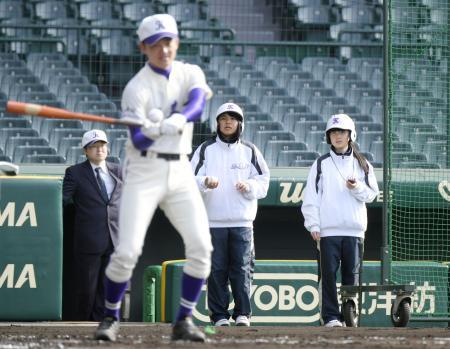 選抜高校野球大会の甲子園練習で、ヘルメットをかぶって補助する不来方の女子マネジャー(右の2人)=14日、甲子園球場