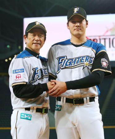 開幕投手を務めることが決まり、栗山監督(左)と握手する日本ハム・有原=札幌ドーム
