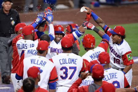 ベネズエラ戦の8回、ソロ本塁打を放ったドミニカ共和国のクルーズ(中央)を祝福するチームメイト=サンディエゴ(ロイター=共同)