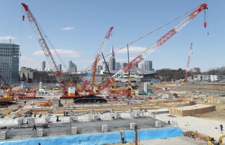 報道陣に公開された新国立競技場の工事現場。中央奥は東京・新宿の高層ビル群=24日午前