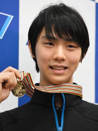 ヘルシンキから帰国し、メダルを掲げ取材に応じるフィギュアスケートの羽生結弦選手=4日午後、羽田空港