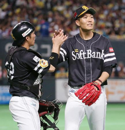 7回の投球を終え、捕手甲斐(左)とタッチを交わすソフトバンク先発の千賀=札幌ドーム