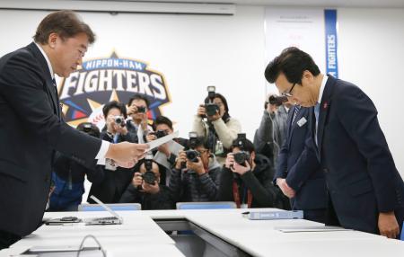 日本ハムの島田利正球団代表(左)に新球場候補地の提案書を手渡し、お辞儀をする秋元克広札幌市長=13日午前、札幌市内の球団事務所