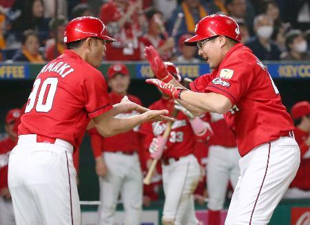 9回、代打で同点本塁打を放ち、コーチ(左)に迎えられる広島・松山=東京ドーム