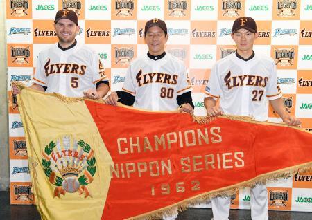 報道陣に東映時代の復刻ユニホームを披露する(左から)日本ハムのレアード、栗山監督、大野=札幌ドーム
