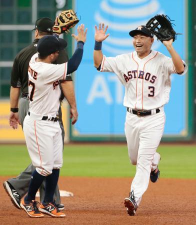 レンジャーズ戦の5回、本塁への好返球で三走の生還を阻み、二塁手アルテューベ(左)と笑顔でハイタッチするアストロズの左翼手青木=ヒューストン(共同)