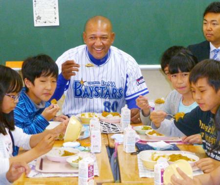 小学生とカレーを食べるDeNAのラミレス監督=15日、横浜市鶴見区の豊岡小