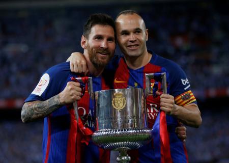 スペイン国王杯のトロフィーを掲げるバルセロナのメッシ(左)とイニエスタ=27日、マドリード(ロイター=共同)
