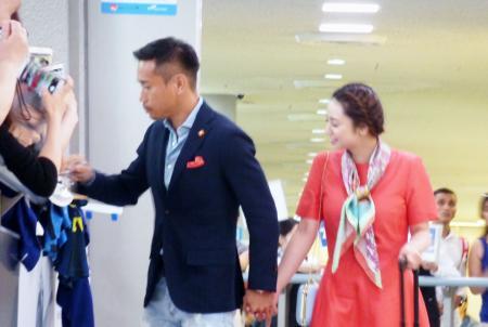 妻で女優の平愛梨さん(右)と帰国し、ファンにサインするサッカー日本代表の長友佑都=30日午前、成田空港