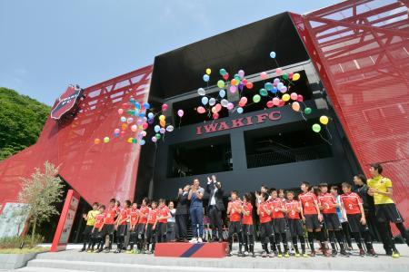いわきFCのクラブハウスがオープンし、完成式典で風船を上げる関係者=10日、福島県いわき市