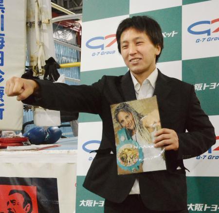 世界初挑戦が決まり、WBC女子バンタム級王者のマリアナ・フアレスの写真を手にポーズをとるぬきてるみ=12日、大阪市