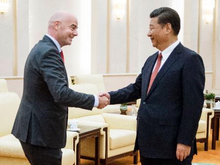 北京の人民大会堂で握手を交わすFIFAのインファンティノ会長(左)と中国の習近平国家主席=14日(共同)