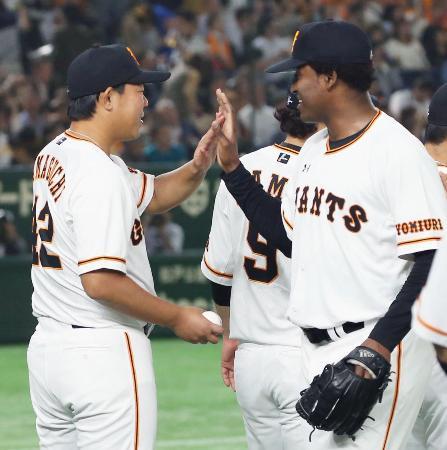 移籍後初勝利を挙げ、カミネロ(右)からウイニングボールを受け取る巨人・山口俊=東京ドーム