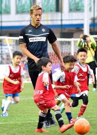 子どもたちとサッカーをする本田圭佑選手=15日、上海(共同)