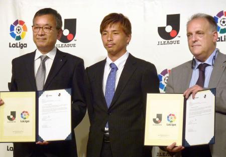 戦略的連携協定を締結したJリーグの村井満チェアマン(左)とスペインリーグのハビエル・テバス会長(右)。中央はエイバルの乾貴士=22日、東京都内