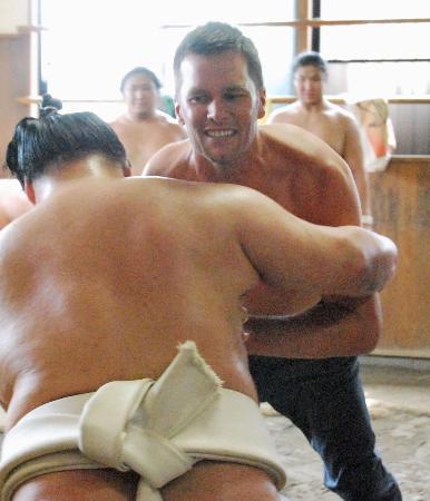 大相撲の境川部屋で、大関豪栄道関(後ろ姿)とぶつかり稽古するNFLペイトリオッツのトム・ブレイディ選手=22日、東京都足立区