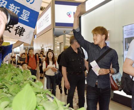 見送りのサポーターに手を振る堂安律=28日午前、関西空港