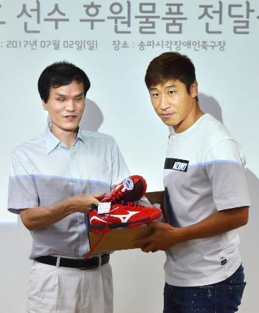 ブラインドサッカーの選手(左)にシューズを贈る李根鎬さん=2日、ソウル(共同)