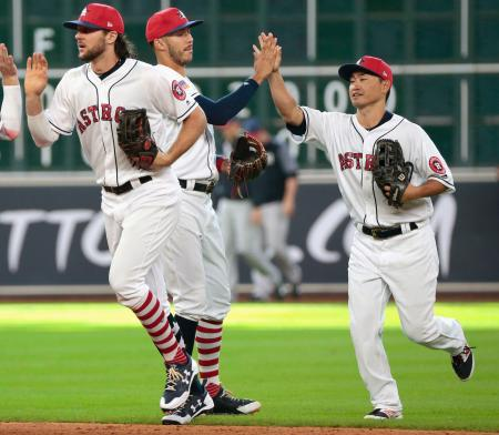 ヤンキースに勝ち、チームメートとタッチを交わすアストロズ・青木(右)=ヒューストン(共同)