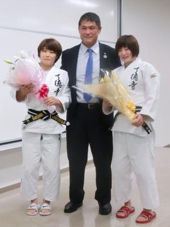 了徳寺学園の壮行会で花束を手にする志々目愛(左)と角田夏実。中央は山田利彦監督=7日、千葉県浦安市