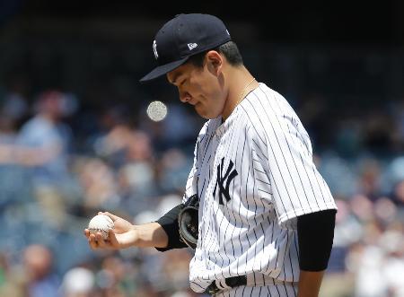 一回に3ランを浴び、ボールを見つめるヤンキースの田中将大=9日、ニューヨーク(AP=共同)