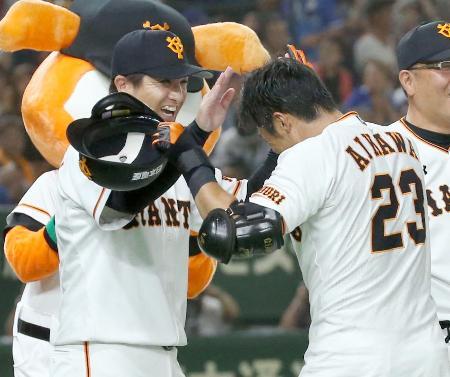 逆転サヨナラ二塁打を放った相川(右)と笑顔でタッチを交わす巨人・高橋監督=東京ドーム