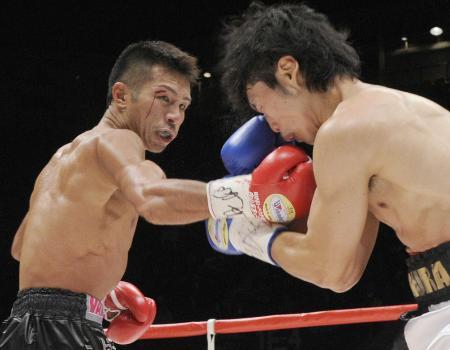 2011年1月、WBAスーパーフェザー級タイトルマッチで、三浦隆司(右)にパンチを浴びせる内山高志=有明コロシアム