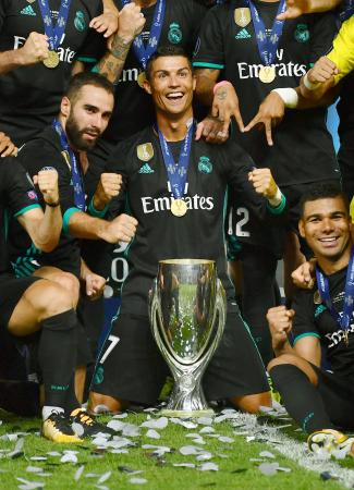 欧州スーパーカップで連覇を果たし、優勝杯を囲むロナルド(中央)らレアル・マドリードの選手たち=スコピエ(ゲッティ=共同)