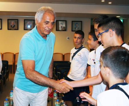 ボスニア・ヘルツェゴビナから来日した子供らと握手するサッカー日本代表のハリルホジッチ監督=9日午後、東京都文京区の日本サッカー協会