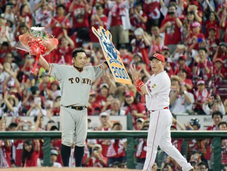プロ野球広島戦で通算2千安打を達成し、花束を掲げる巨人の阿部慎之助内野手。右は祝福する広島の新井貴浩内野手=13日、広島市のマツダスタジアム