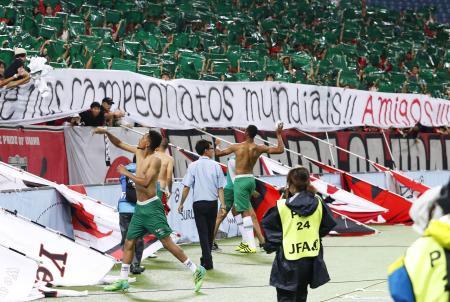 15日の浦和戦で、ポルトガル語の横断幕を掲げる観客の声援に応えるシャペコエンセの選手たち=埼玉スタジアム