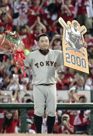 プロ野球広島戦で通算2千安打を達成し、ボードを掲げる巨人の阿部慎之助内野手=13日、広島市のマツダスタジアム