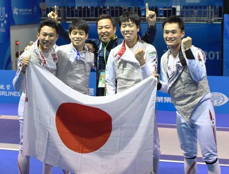 フェンシング男子フルーレ団体で優勝し、ガッツポーズする(左から)西藤、野口、青木コーチ、敷根、松山=台北(共同)