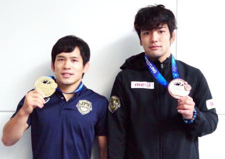 世界選手権で獲得した金メダルを手にする高橋侑希(左)と銅メダルの藤波勇飛=28日、羽田空港
