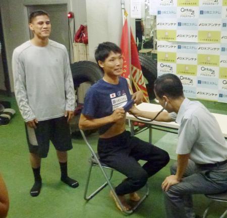 防衛戦に向け予備検診を受けるWBAスーパーバンタム級王者の久保隼(中央)。左は挑戦者のダニエル・ローマン=31日、神戸市