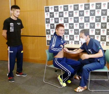 予備検診を受けるIBFスーパーバンタム級王者の小国以載(中央)。左は挑戦者の岩佐亮佑=11日、大阪市