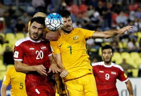サッカーのW杯アジア予選プレーオフ第1戦、ヘディングで競り合うオーストラリアとシリアの選手=5日、マレーシア・メラカ(ロイター=共同)