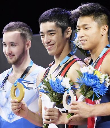 男子種目別床運動で優勝し、表彰式で金メダルを手にする白井健三(中央)=モントリオール(共同)