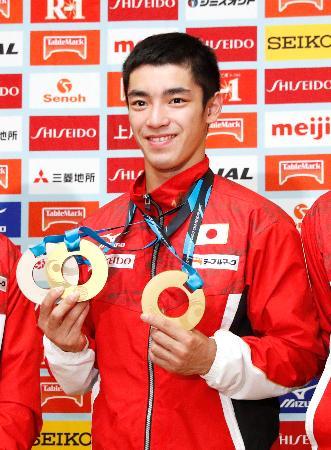 カナダで行われた体操の世界選手権から帰国し、記者会見でメダルを手にする白井健三=10日午後、成田空港