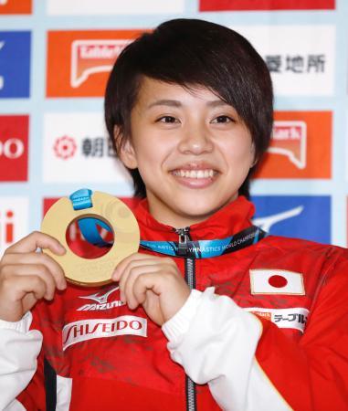 体操の世界選手権から帰国し、記者会見で金メダルを手にする村上茉愛=11日夜、東京都渋谷区