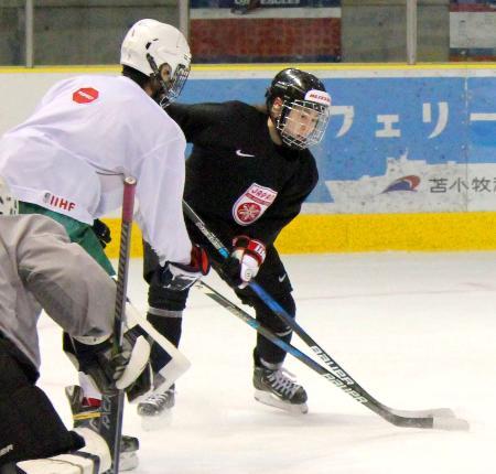 アイスホッケー女子日本代表の合宿で、男子高校生(左)と競り合う米山=白鳥王子アイスアリーナ