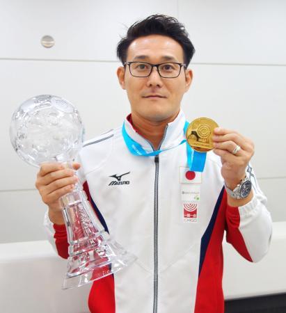 帰国し、メダルを手に取材に応じる松田知幸=31日午前、成田空港