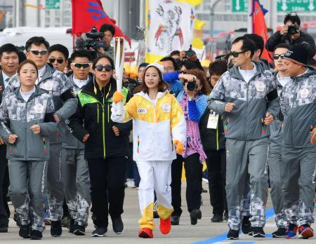 平昌冬季五輪の聖火リレーで、第1走者を務める韓国フィギュアスケート女子の劉永(中央)=1日、仁川(共同)