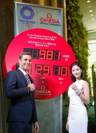 東京・銀座に設置されたオメガの東京五輪カウントダウン時計の前でポーズをとるチャド・レクロー選手(左)と女優の菜々緒さん=16日午前