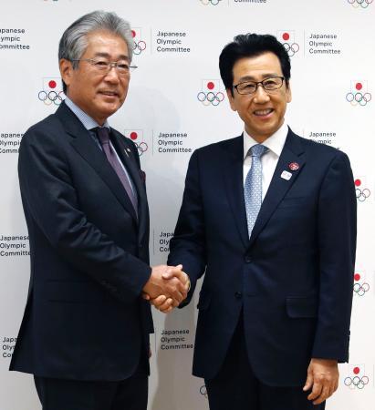 記者会見後に握手する札幌市の秋元克広市長(右)とJOCの竹田恒和会長=22日午後、東京都新宿区