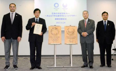 感謝状を受け取り、記念撮影に応じる静岡県の川勝平太知事(左から2人目)=24日、東京都港区