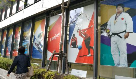 パラ競技団体を支援する「日本財団パラリンピックサポートセンター」には選手たちがディスプレーされ、道行く人にPRしている=28日、東京都港区