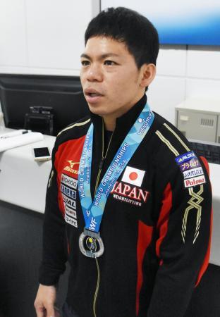 重量挙げの世界選手権から帰国し、取材に応じる男子62キロ級銀メダルの糸数陽一=4日午後、成田空港
