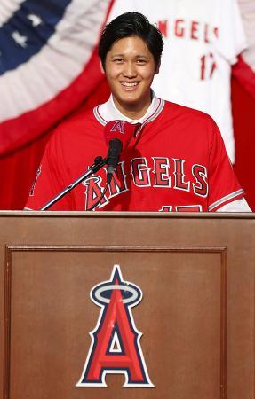 米大リーグ、エンゼルスの入団記者会見で、ユニホームを着て笑顔の大谷翔平選手=9日、エンゼルスタジアム(ゲッティ=共同)