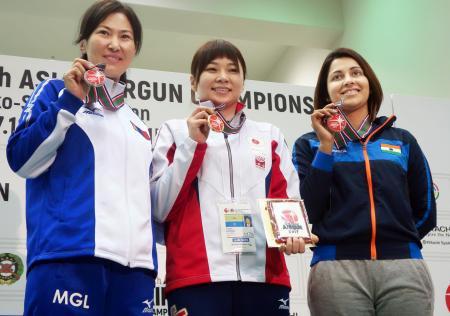 女子10メートルエアピストルで初優勝し、メダルを手に笑顔の小西ゆかり(中央)=和光市総合体育館
